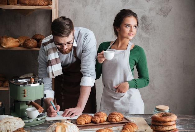 Yong homem e mulher tentando cozinhar pão