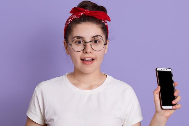 Yong, linda mulher, em pé, isolada em um espaço lilás com empolgação, segurando o telefone, usando roupas casuais e óculos
