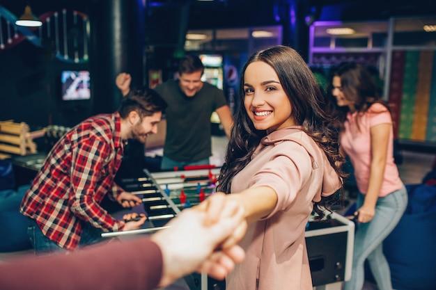 Yong linda mulher sorrindo. ela está na sala de jogos. modelo segura a mão do homem. as amigas dela ficam na mesa de futebol e brincam.