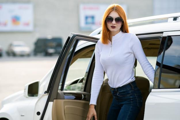Yong mulher bonita em pé perto de um grande carro todo terreno ao ar livre. garota de motorista em roupas casuais fora de seu veículo.
