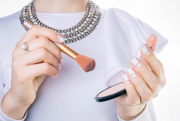 Yong mulher vai aplicar rouge ou pó. produto de maquiagem