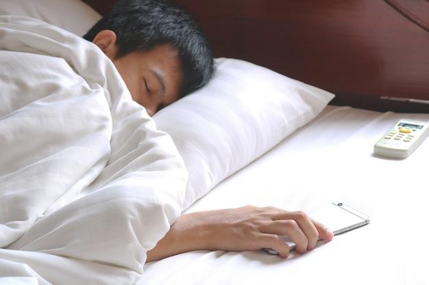 Yonng homem dormindo no quarto e telefone lidar com controle remoto de ar condicionado.