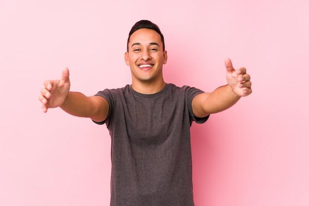 Yooung homem latino posando em uma parede rosa se sente confiante dando um abraço