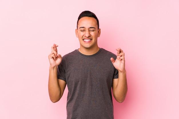 Yooung latino homem posando em um fundo rosacrossing dedos para ter sorte