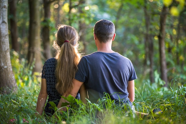Youg casal, homem e uma mulher sentados juntos ao ar livre curtindo a natureza.