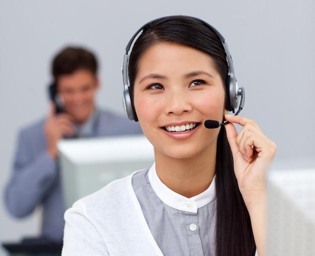 Youg empresária asiática com fone de ouvido em sua mesa