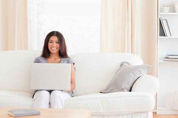 Youg mulher com caderno em um sofá