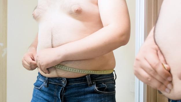 Yougn gordo medindo a barriga de feto grande com fita métrica. conceito de excesso de peso masculino, perda de peso e dieta.