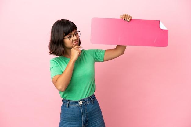Youing mulher segurando um cartaz vazio e pensando