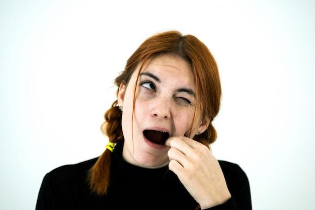 Youn mulher com a boca aberta, cavando com os dedos por algo preso nos dentes depois de comer.