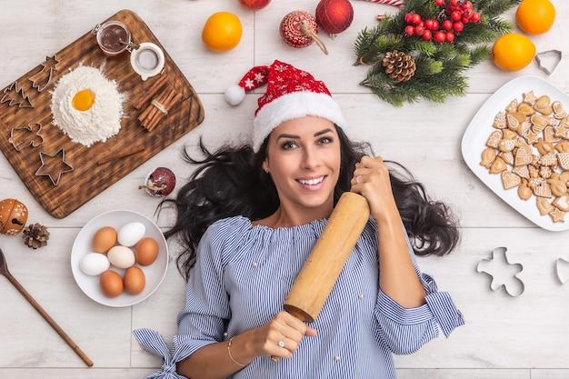 Yound e mulher feliz segurando firmemente um rolo enquanto deitada no chão com coisas temáticas como: ingredientes de natal, farinha e ovo, laranjas, formas de cozimento e chapéu de papai noel vermelho.