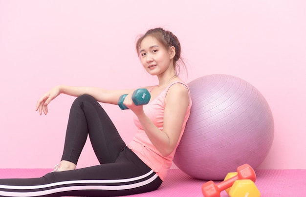 Younf bonito garota levantando halteres em fundo rosa