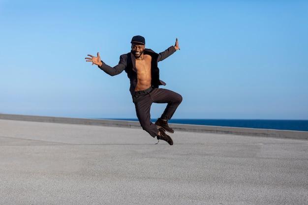 Young bl ck m vestindo roupas casuais pulando.