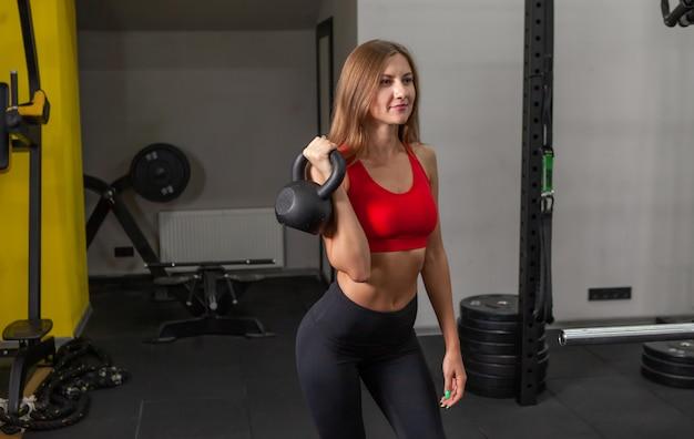 Young cabe mulher em roupas esportivas segurando kettlebell pesado no ginásio moderno. treinamento de pesos livres
