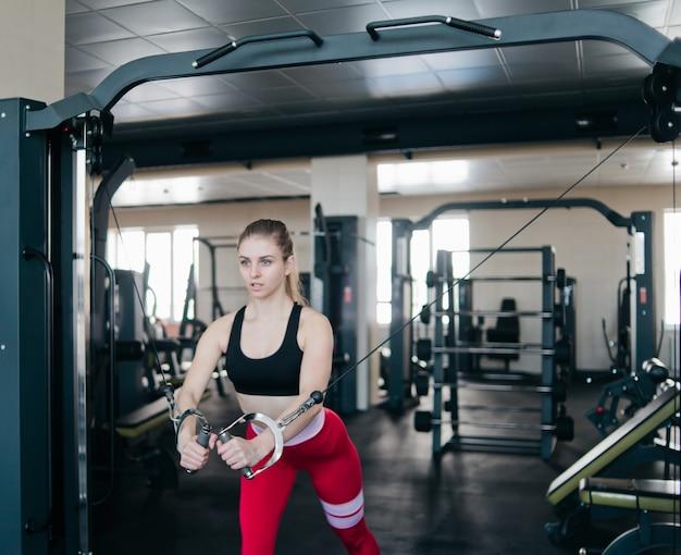 Young cabe mulher fazendo exercício na máquina crossover no ginásio