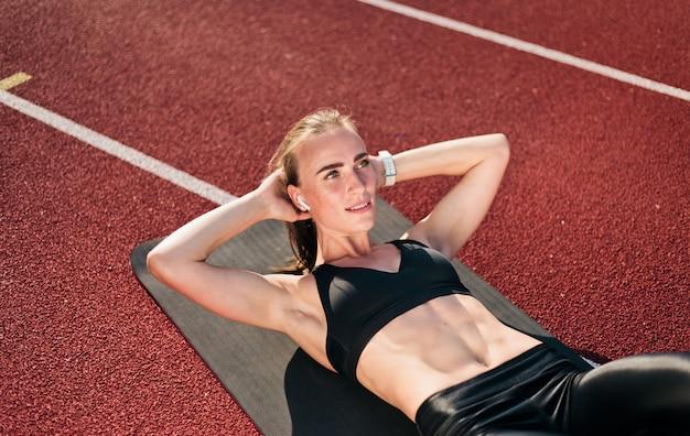 Young cabe mulher perfoms seu corpo fazendo exercício de torção para os músculos abdominais na esteira na pista do estádio com revestimento vermelho
