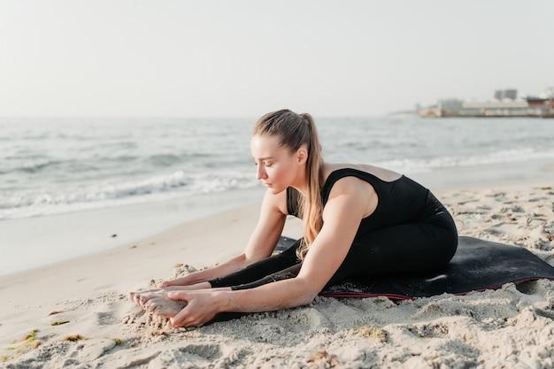 Young cabe mulher prática yoga asana na areia perto do oceano