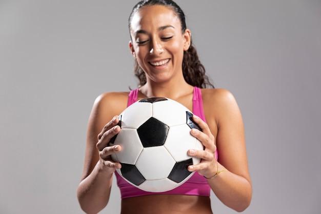 Young cabe mulher segurando bola de futebol
