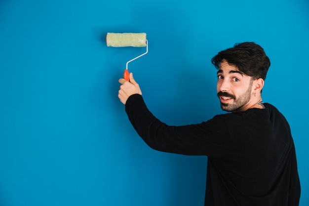 Young painting painting wall Foto gratuita
