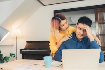 Young salientou casal asiático gerenciando as finanças, revendo suas contas bancárias usando o computador portátil
