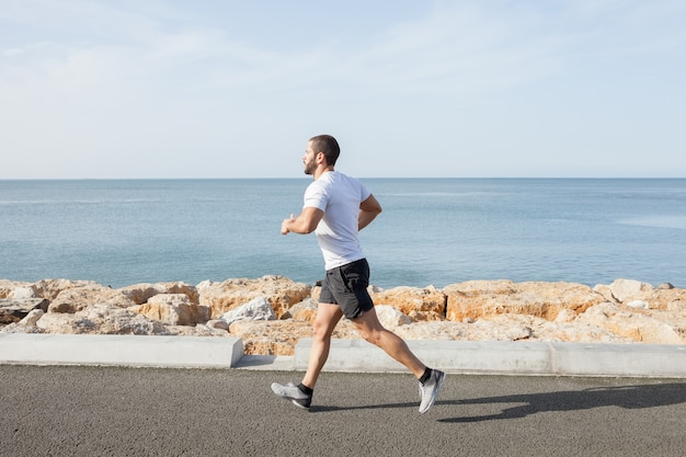 Young strong sporty man running on road ao longo do mar