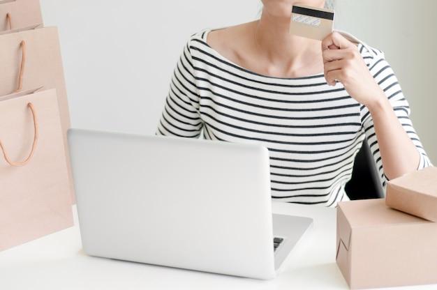 Young woman shopping online com cartão de débito / cartão de crédito, pagamento e conceito de marketing