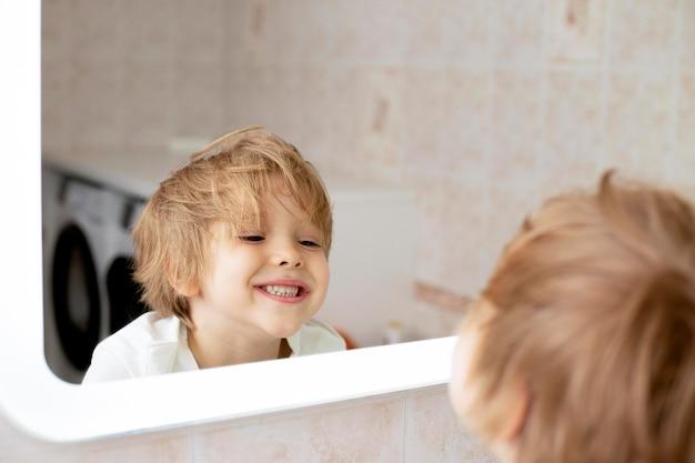 Younn menino no banheiro olhando no espelho
