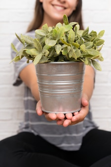 Younng mulher em uma casa tomando um vaso