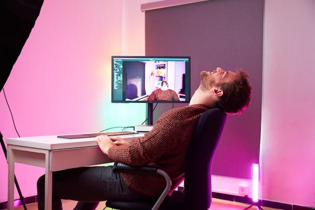 Youtuber sentado na cadeira de sua configuração enquanto ri se recostando