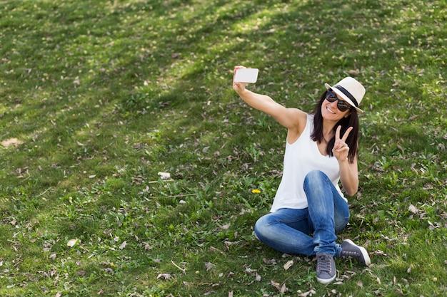 Ypoung linda mulher tirando uma foto com uma vara de selfie. se divertindo conceito. ela está usando chapéu e óculos escuros.