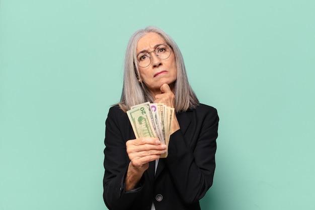 Ysenior bonita empresária com notas de dólar.