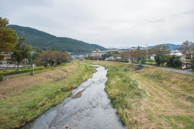 Yufuin aldeia, rio, yufu montanha e céu azul com fundo de nuvem, yufuin, oita, kyushu, japão