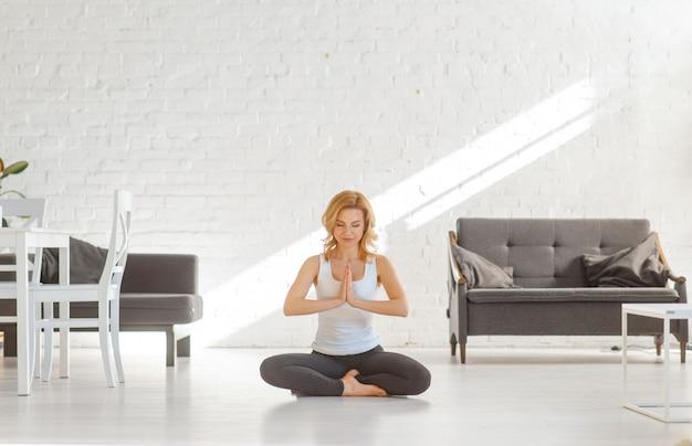 Yuong mulher sentada no chão em pose de ioga