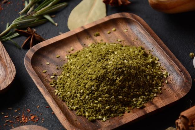 Za'atar uma mistura de especiarias que inclui a erva junto com sementes de gergelim torradas e sumagre seco em uma placa de madeira