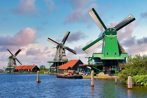Zaanse schans, países baixos - cerca de agosto de 2020: moinho holandês na zona rural verde perto de amsterdam, com céu azul e água do rio.