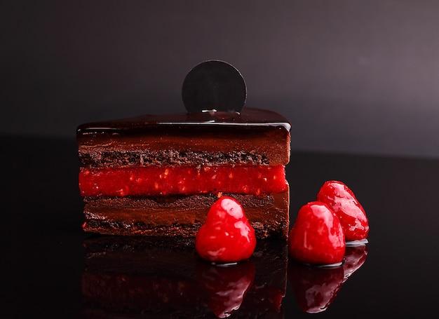 Zacher do bolo de chocolate com framboesa, musse na reflexão de espelho, seção. sobre o fundo preto.