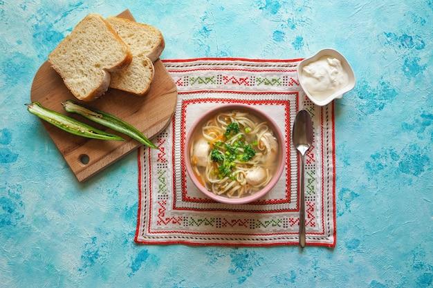 Zama, sopa de galinha romena e moldava com macarrão. a sopa tradicional de ressaca é servida com pimenta e creme de leite.