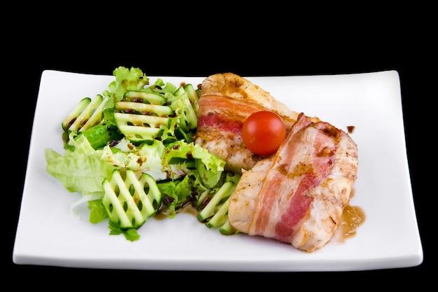Zander tenro em bacon: filé, bacon defumado, molho de romã narsharab, pepino, folhas de alface. close-up em uma placa branca em fundo preto