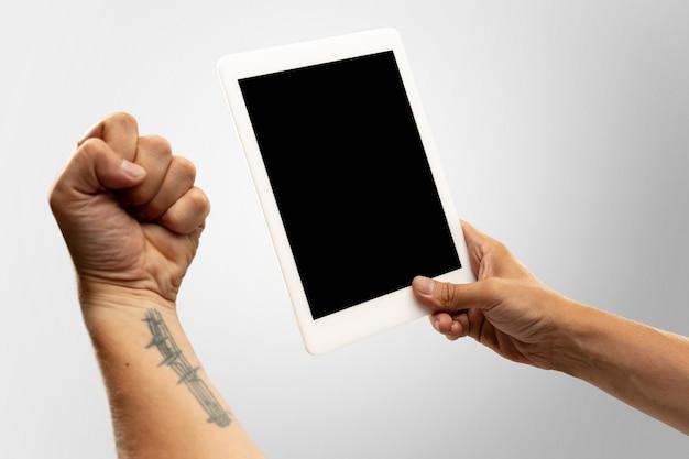 Zangado, emocional. feche as mãos masculinas segurando um tablet com tela em branco durante a exibição on-line de jogos de esporte popular, campeonatos. copyspace para anúncio. dispositivos, gadgets, conceito de tecnologias.