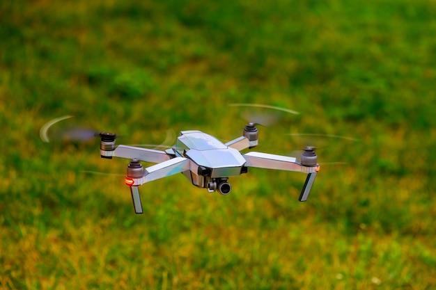 Zangão com a câmera profissional do cinema que voa sobre o parque do verão.