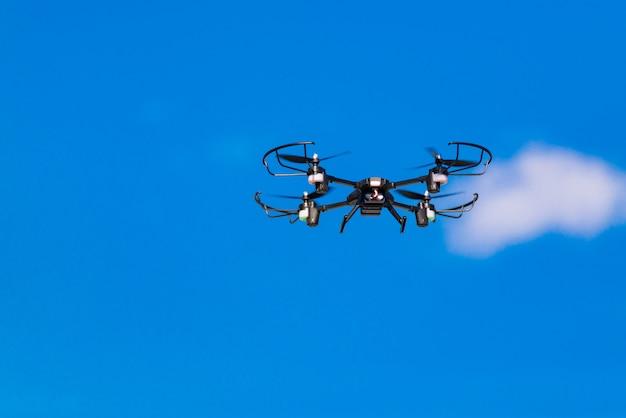 Zangão do voo ou helicóptero do quadrilátero no céu azul.
