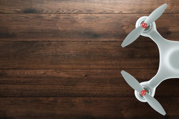 Zangão, quadrocopter branco no fundo de madeira, marrom com espaço da cópia. vista superior, la plana