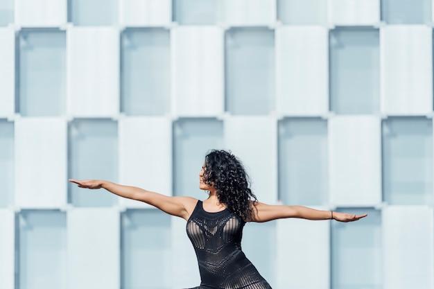Zé bonito mulher praticando ioga na cidade grande entre edifícios.