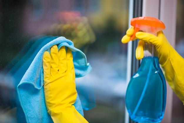 Zelador com luvas amarelas, janela de vidro de limpeza