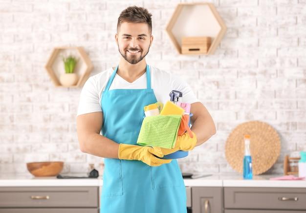 Zelador com material de limpeza na cozinha
