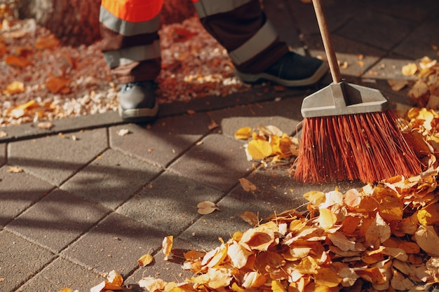 Zelador de limpeza varrendo folhas de outono na rua