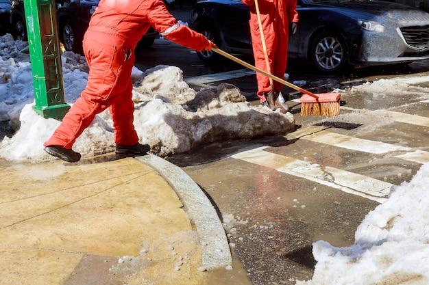 Zelador limpa a rua de neve pela manhã