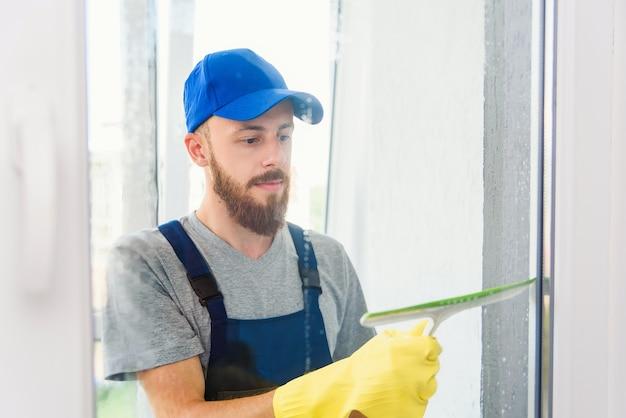 Zelador masculino usando um rodo de borracha para limpar uma janela em um escritório usando um avental e luvas enquanto ele trabalha