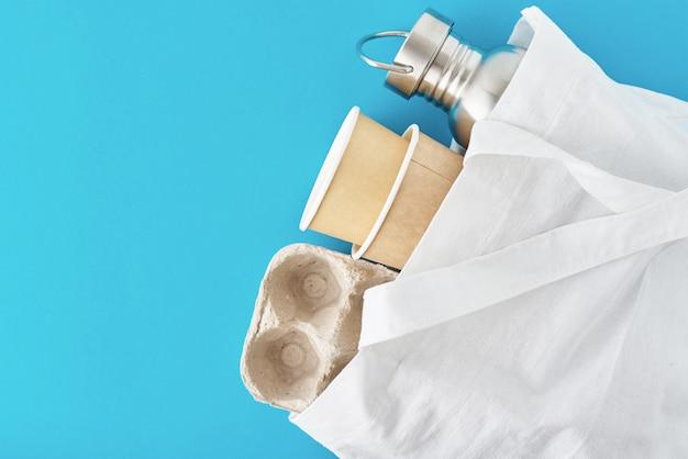 Zero conceito de desperdício. eco amigável itens reutilizáveis na sacola de compras natural. bandeja de ovos de papel, xícaras de café e garrafa de metal em um azul
