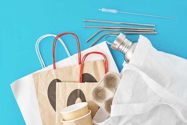 Zero conceito de desperdício. itens reutilizáveis ecológicos em sacola de compras natural. saco de papel e xícaras de café, garrafa de alumínio e tubos de metal